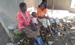 Harriet Nabukwasi (right) explains to her neighbour how a solar lamp works