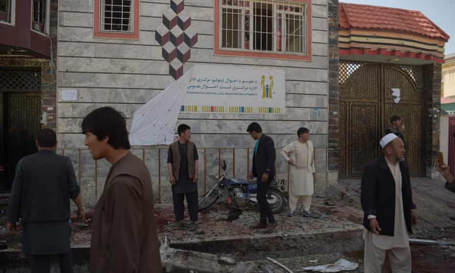 Afghan residents inspect the site of a suicide bombing outside a voter registration centre in Kabul on Sunday