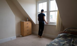 A young male, who is an unaccompanied asylum seeker, stands his bedroom