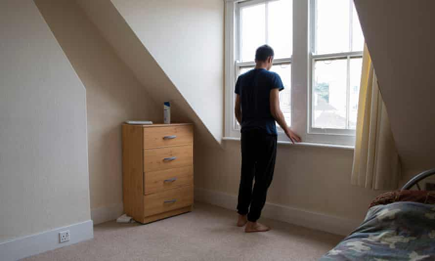 A young male, who is an unaccompanied asylum seeker, stands his bedroom in Kent, UK.