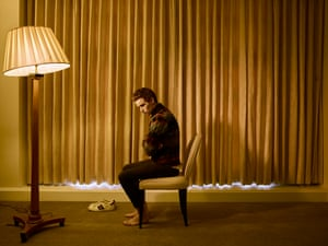 die Redmayne sits, arms folded, slightly hunched, on a dining chair, seen in profile, a long drawn gold curtain behind him