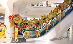 a dragon rides the escalator in a Bangkok shopping mall for Chinese new year.