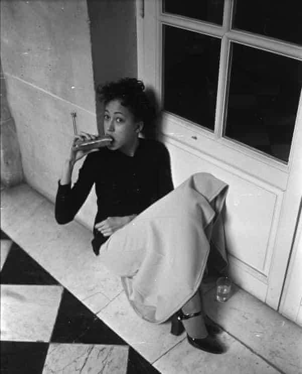 Pat Cleveland eating a sandwich at the Battle of Versailles in 1973