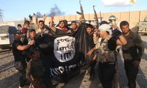 Iraqi security forces and allied Shiite militiamen celebrate as they hold a flag of the Islamic State group they captured in Tikrit, 80 miles (130 kilometers) north of Baghdad, Iraq, Tuesday, March 31, 2015.