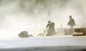 Security forces run from the scene of a suicide attack in Kabul on Monday.