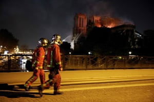 Firefighters look a fire at the landmark Notre-Dame Cathedral as they cross a bridge over the Seine river