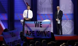 Pete Buttigieg, left, listens to protesters along with CNN moderator Anderson Cooper as he speaks during the Power of our Pride Town Hall.