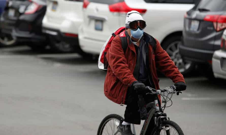 A person wearing a mask bikes away from the Life Care Center of Kirkland in Washington on 3 March.