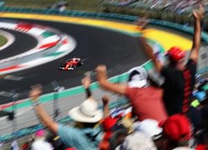 Fans cheer as Raikkonen rounds the final corner during qualifying.