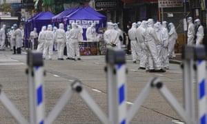 Government investigators wearing protective suits gather in the Yau Ma Tei area in Hong Kong