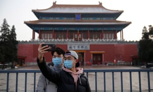Tourists wearing face masks take a selfie outside of the Forbidden City in Beijing, China. The coronavirus has so far claimed at least 300 lives and infected more than 14,000 others.