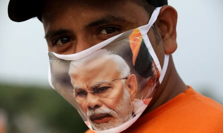 An Indian man wears a mask with a picture of Modi