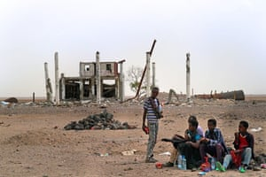 Migrants rest amid the ruins of a bombing, roughly 80km inland on the journey to Aden
