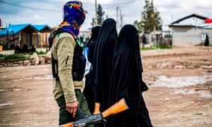 Foreign women, living in al-Hol camp which houses relatives of Islamic State (IS) group members, walk under the supervision of a fighter of the Syrian Democratic Forces (SDF) in the camp in northeastern Syria on 28 March 2019.