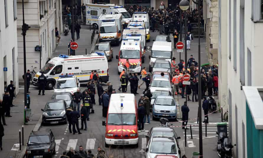 Firefighters, police officers and forensic teams outside the offices of Charlie Hebdo in Paris on 7 January 2015.