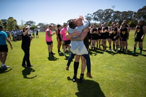 Tasmanian senator Jacqui Lambie gets a bear hug from one of the Tasmanian police AFL players at the 31st National Police Football Championships in Canberra