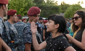 An Armenian opposition member stand in front of military forces during a protest in central Yerevan.
