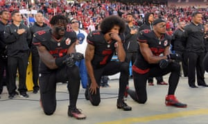 Colin Kaepernick, center, protests before a game against the Arizona Cardinals last October.