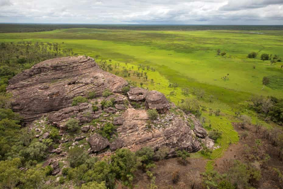 An aerial view of Ubirr rock formation and the surrounding savanna during the wet season, as seen from a helicopter over Kakadu national park