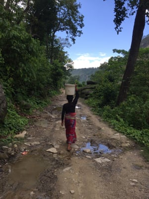 A woman carries water to Tatopani, Surkhet, Nepal