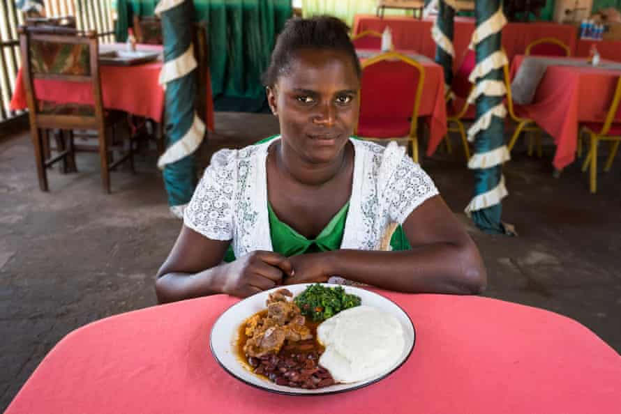 Elvas Munthali, with her meal of nsima, chicken, beans and spinach