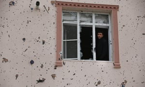 A man looks out of a window damaged by a rocket fired by Kurdish fighters in Syria into the town of Kilis, Turkey.
