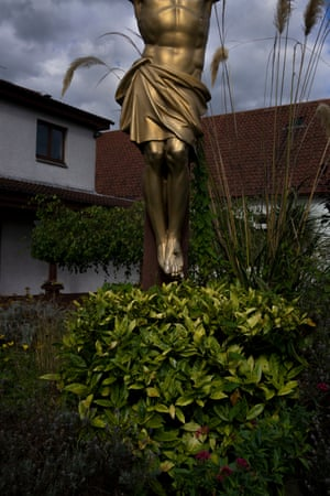A statue of Jesus Christ hangs above hedging in Warriston.