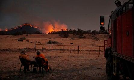 two people watch a bushfire