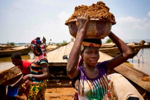 Women unload river sand from boats moored in the port of Bamako