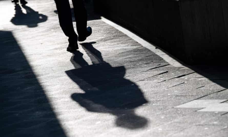 A man casts a long shadow on the pavement