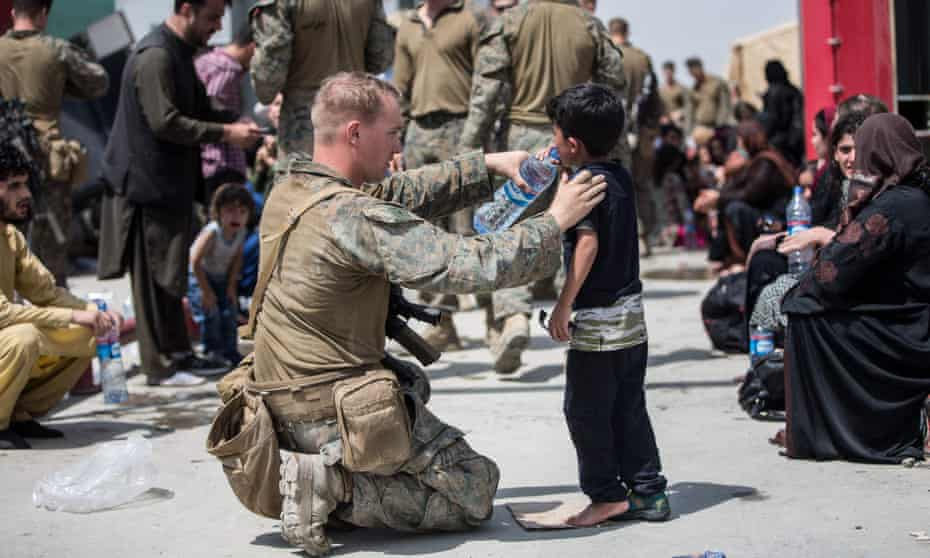 A US marine provides fresh water to a child during an evacuation at the airport in Kabul on Friday.