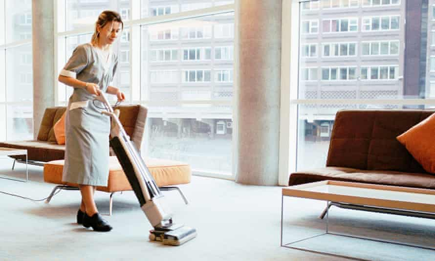 A cleaner vacuuming a conference venue