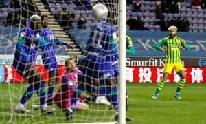 Charlie Austin (right) earns a point for West Brom at Wigan but it was not enough to take them back above Leeds at the top of the Championship.