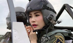 The Thai royal noble consort Sineenat Wongvajirapakdi adjusting her pilot's helmet in a military aircraft during a training session