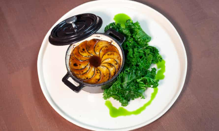 A dish of oxtail and potato hotpot on a round white plate with green veg to the side