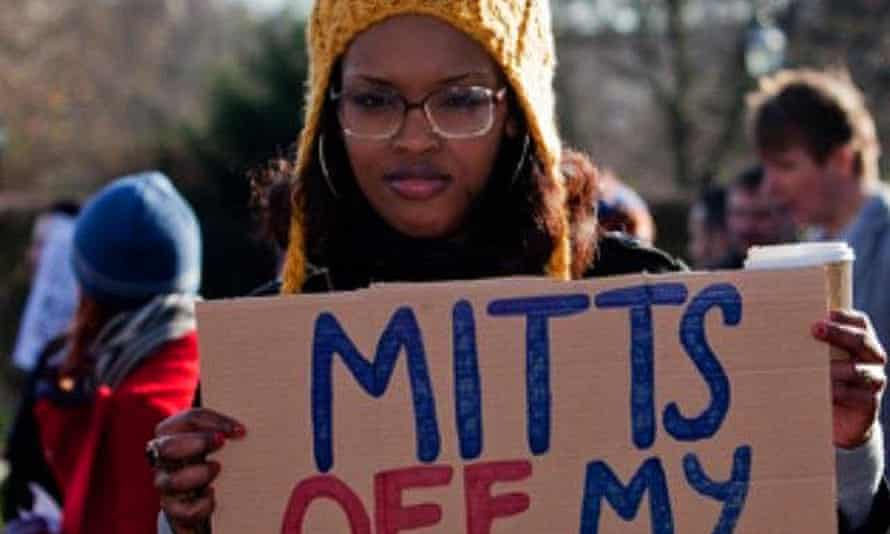 Activist Nimco Ali holds a banner saying 'Mitts off my muff'