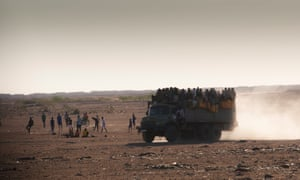 A truck of passengers on the road to Libya is scarcely visible in the sand.