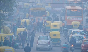 Indian commuters travel on a polluted road near a bus terminus in Delhi.
