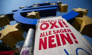 A banner urging a no vote in Sunday's referendum in Greece hangs from a euro sign monument in front of the former European Central Bank headquarters in Frankfurt.