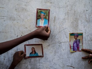 Family members hold up photos of Paulina, 42, who was abducted four months ago during a Boko Haram attack. Since then her family have had no news of her.