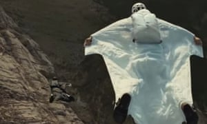 A Saudi woman wearing a wingsuit launches herself from a cliff
