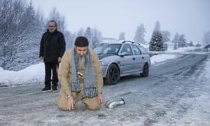 Mullah Krekar kneeling on a road