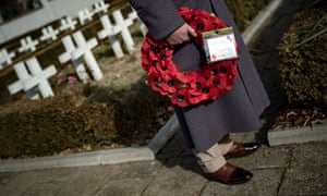 A British  officer holds a wreath of poppies at the French soldiers' cemetery in Belgrade