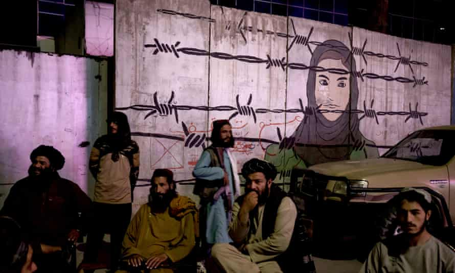 Taliban members in front of a mural depicting a woman behind barbed wire in Kabul, Afghanistan