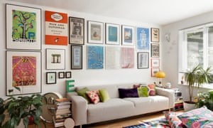Eduardo and Mauricio's sitting room with long beige sofa, colourful cushions and large framed pictures lined up on the wall above
