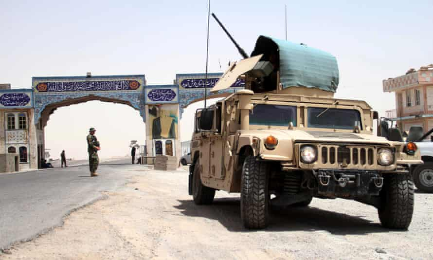 Afghan National Army (ANA) soldiers stand guard on a road side check point in Herat, 10 July 2021