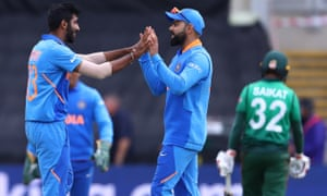 Jasprit Bumrah (left) of India is congratulated by captain Virat Kohli after taking the wicket of Mosaddek Hossain.
