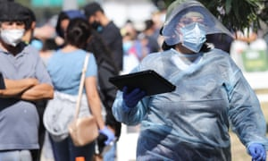 A worker in personal protective equipment helps check in people at a Covid-19 testing centre at Lincoln Park amid the coronavirus pandemic on July 7, 2020 in Los Angeles, California.