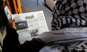 A Palestinian man reads a local newspaper with news of the Israeli election, in Hebron, in the Israeli-occupied West Bank.