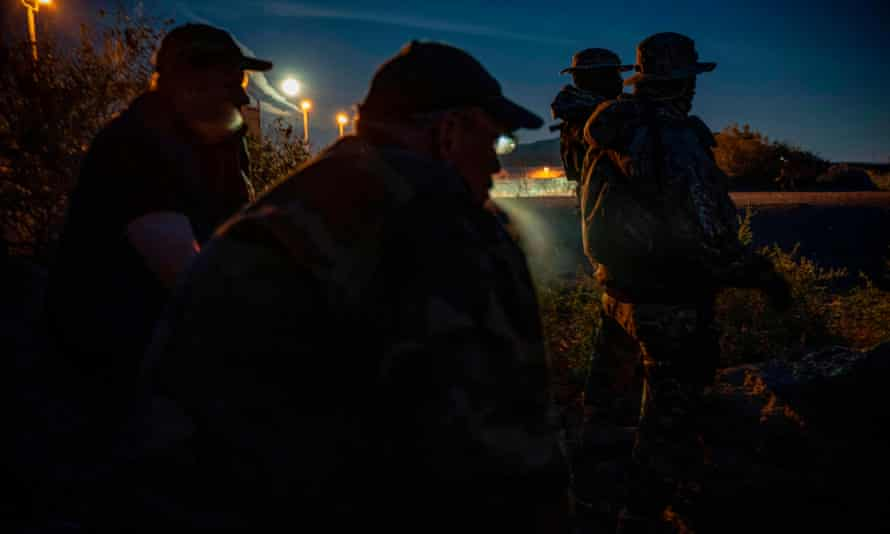 Men including Jim Benvie, a spokesman for the militia calling itself the United Constitutional Patriots, share cigarettes while patrolling the US-Mexico border in Sunland Park, New Mexico last month.
